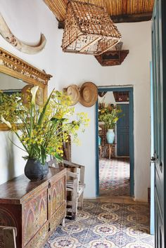An entry laid with 19th-century Spanish cement tiles rescued from a now-demolished villa in Tangier. The light fixture is a cage for transporting pigeons, and on the wall, a whale rib hangs over a Regency mirror found in a flea market. (Photo: Ngoc Minh Ngo)