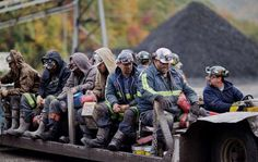 Coal miners return on a buggy after working a shift underground - David Goldman/AP