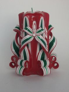 This hand-carved Christmas pillar has a green and white striped interior and a bright Christmas red exterior. Christmas Candles, Red Christmas, Christmas Ornaments, Red Candles, Pillar Candles, Three Color Combinations, Bow Pattern, Amazing Decor, Beautiful Candles