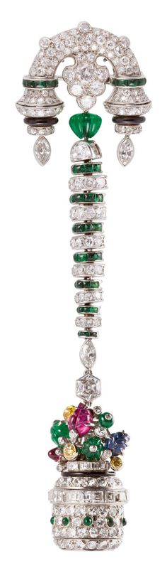 MAUBOUSSIN - AN EXQUISITE ART DECO TUTTI FRUTTI PENDANT WATCH, CIRCA 1925. The bow motif set with single-cut diamonds, onyx, enamel and calibré emeralds supporting flexible links set with diamonds enamel and emeralds continuously suspending a flower basket set with old-mine, old European, single-and square emerald-cut diamonds, the basket filled with round cabochon and carved rubies, sapphires and emeralds, and diamonds, and black onyx.