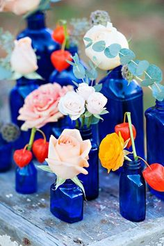 assorted blue glass bottles with single or simple flowers from Pretty Little Wedding Things