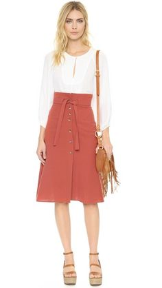 A high-rise Loup skirt in a classic A-line silhouette. The button closure ends at a notched vent, and a self-belt accents the wide waistband. Unlined.