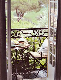 Balcony with curvaceous iron railing and room for two and a liquid refreshment, depending on time of day!  via oliveaux blog