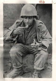"""Lawrence Warner takes time out to eat a tin of K rations beside the entrance of his pillbox """"home"""" near Irrel, Germany. United States Army, Press Photo, War Machine, Us Army, World War Ii, American History, Wwii, Germany, Military"""