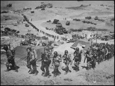 Omaha Beach, June 1944  Amazing photo depicting the line up of men making their way...