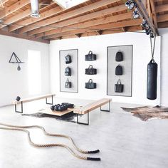 To keep your home gym studio from looking dark and unwelcoming, keep the contrast with bright white walls, black equipment, and neutral accents like rope and benches. #HomeGyms