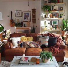 Warm and inviting space. The leather sofa with it's mix of pillows...green plants...shelves with things to attract the eye.
