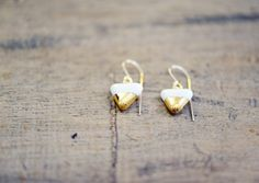 These are tiny triangular earrings, formed to look like little pennant flags. Highlighted with 22k gold dipping and dangling from hand-shaped