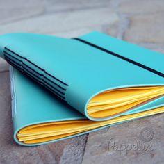 Caderno em capa de courino azul, miolo em papel ColorPlus amarelo e costura tipo Longstitch, com acabamento em elástico