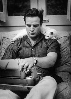 Marlon Brando with typewriter and cat.