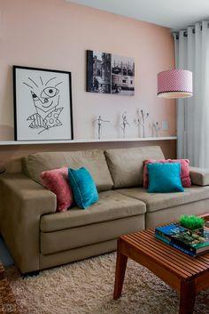 Prateleira + adornos: para expor seus objetos preferidos, Viviane Gullo, investiu em uma prateleira de gesso logo acima do encosto do sofá, com estrutura interna de ferro, foi chumbada em um recorte na alvenaria. Ali repousa sua coleção de estatuetas e um dos quadros mais queridos. Fixada no teto, a luminária teve a cúpula customizada com tecido cor-de-rosa, tom que realça a cor da parede. Sobre o tapete felpudo, a mesinha de centro, que era preta, foi lixada para exibir a estrutura de freijó.
