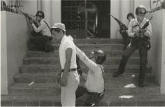 National Policeman Using Ice-Cream Vendor as a Shield During Skirmish with Demonstrators, San Salvador — Etienne Montes.  El Salvador : Work of Thirty Photographers (1983). CSUSM.