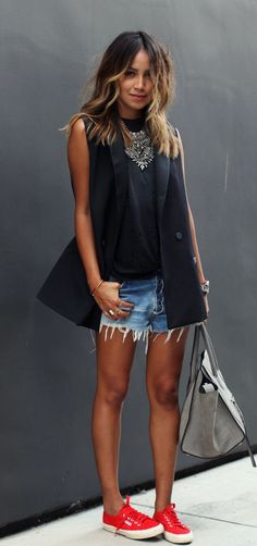 Julie Sarinana is wearing a black oversized sleeveless jacket from Madewell, matching tank from Hye Park and Lune, denim cut offs and red sneakers from SuperGa