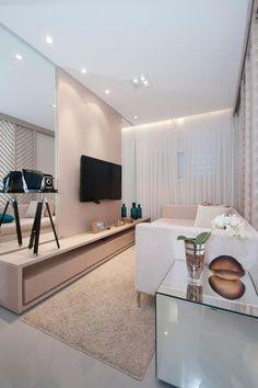 Em sintonia com as tendências, o rosa seco foi a cor escolhida para o painel e o rack da TV. A sala de estar é pequena e estreita, e o espelho na parede amplia visualmente o ambiente. (decoração living room rose home theater)