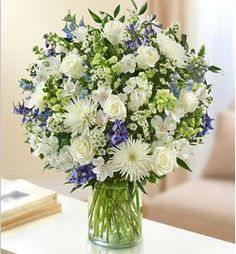Sincerest Wishes Blue and White Arrangement Beautiful in blue and white, our abundant fresh flower arrangement is crafted of elegant roses, snapdragons, delphinium, stock, alstroemeria, spider mums an