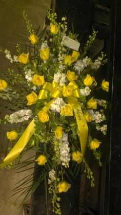 Funeral spray in yellow and white for a Mom that will be missed. americasflorist.com