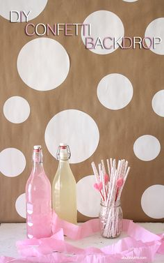 CONFETTI BACKDROP:  Materials:  Roll of Kraft Paper/  Roll of Contact Paper in desired color(s)/  Large Circle Cutter/  Self Healing Mat/   Thumbtacks or tape for hanging.  (Tute)