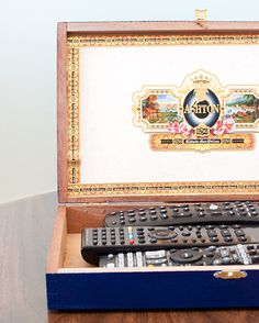 Awesome idea to store all of our remotes...paint an old cigar box, and voila! Love it.
