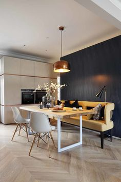 """Modern home with Dining Room, Pendant Lighting, Chair, Table, and Light Hardwood Floor. Adding wood floors to the home proved to be a challenge, both in terms of approval and execution. Since the flat is located in a historic mansion block, the license to alter it was very strict. Once approved, floating oak parquet floors were installed above a high-performance acoustic system to offer sound insulation for the neighbor below. The open dining room exemplifies the clients' wish for a """"fun yet…"""