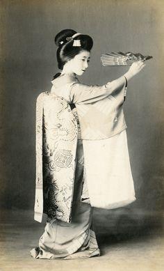 Dragon and Pearl Obi, ca. 1910. Maiko (Apprentice Geisha) Momotaro, dancing with a mai-ogi (dancing fan), her obi (sash) decorated with dragons and pearls. °