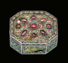 A MUGHAL RUBY-SET ENAMELLED GOLD PAN-BOX, PROBABLY LUCKNOW, EARLY 19TH CENTURY  Of octagonal shape, set with teardrop and circular shape rubies to lid on a ground of pink and white enamelled floral sprays with green leafs, a border of repeating similar surrounding, the sides with square and rectangular cartouches containing enamelled scenes of birds and various animals