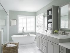 Stunning bathroom features a gray-green grasscloth papered walls over a gray bathroom vanity with center console cabinet accented with polished nickel hardware alongside white quartz counters which frame his and her sinks with polished nickel medicine cabinets above. An oval freestanding tub with floor mounted tub filler below plantation shuttered windows at the far end of the space atop rectangular white marble tiled floors next to large seamless glass shower.