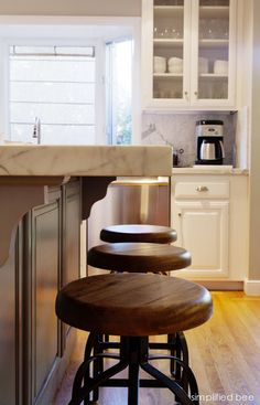 white carrara marble counter-top // kitchen island.  Love the art bar stools too!