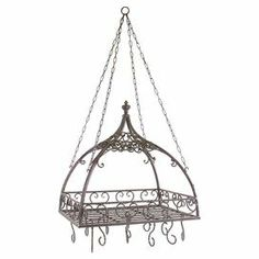 "Bring stylish organization to your kitchen with this versatile pot rack, showcasing scrolling iron work in a rust hue.    Product: Pot rack  Construction Material: Wrought iron Color:  RustFeatures: Domed with hooks Features open metal-work designDimensions: 23"" H x 24"" W x 17.75"" D"