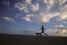 A Woman And Her Dog Run Along The Beach