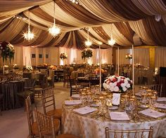 Gilded table décor dresses up an elegant brown and white tent lit with dangling chandeliers.