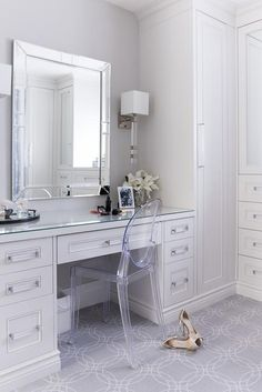 White and gray dressing room features a built-in make up vanity adorned with glass pulls paired with a Kartell Victoria Chair placed under a beveled mirror illuminated by Regina Andrew Metropolitan Crystal Sconces.