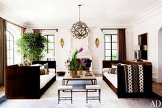 Brown and white couches, brown and white printed pillows with matching throw blanket, white rug, white walls, brown curtains, and circular brown chandelier