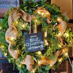 """Want to add a little personality to your Christmas wreath? Dress it up with cinched burlap ribbon, battery-operated icicle lights, and a message square hung from the top with twine. Get into the spirit of the season with festive messages, such as """"Out Christmas Shopping,"""" """"Happy Holidays,"""" or """"Baby It's Cold Outside."""""""