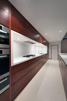 Eccellente contrasto tra il bianco e il mogano ampiamente utilizzato in questa cucina moderna