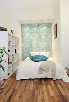 The feminine-looking home uses subtly demarcated areas by fitting a bed in a hidden corner of the living room