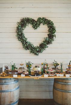 Brides.com: . A handmade dessert table on large barrels with heart-shaped greenery featuring panna cotta spoons, chocolate truffles, and fruit tarts.