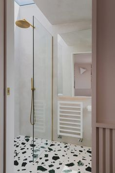 Graphic black and white terrazzo floor tiles feature alongside pale-toned plaster walls. The room also boasts a large skylight, located above the walk-in shower.