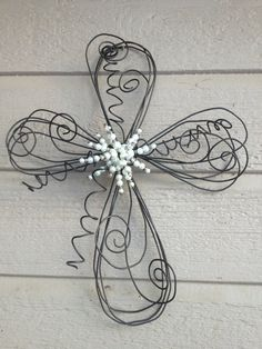 Elegant and whimsical, this twisted wire cross with elegant pearl beaded center adds a shabby chic decorative touch to your front door, wall or gateway. Beaded center is made with glass pearl beads and silver bead caps. Cross is made from bailing wire individually twisted so each one is unique and different! Can be displayed outdoors - but if exposed to rain it will rust! Which depending on your point of view rust can be divine! :) Approx. 15Lx12W