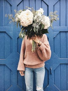 instagram photo ideas for fashion boutiques | flowers in hand against wall backdrop