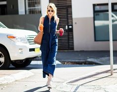 Statement sunglasses are paired with a zip-up denim dress and strappy sandals