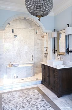 Amazing Bathroom Features An Arched Glass Shower Clad In White Marble Tiles  Lined With A Brizo Virage Shower System In Brilliance Brushed Nickel.