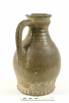 Mid-late twelfth century. Coarse London-type ware early rounded jug with reduced, clear glaze, cordonned neck, thumbed base and herringbone-stabbed rod handle. London Museum