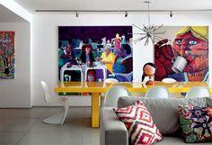 Na sala, a mesa de jantar laqueada de amarelo (Micasa) se alinha às telas de Arthur Arnold e Nunca.