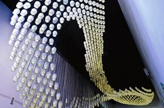 """Aidia Studio, an architecture and design firm founded by Rolando Rodriguez-Leal and Natalia Wrzask, installation Milkywave. The piece consists of 1,664 ceramic yogurt bottles that have been repurposed as a multi-story hanging light fixture...illuminated from within..the unified entity, the installation as a whole, that significantly brightens a room...The project's intention is to present a beautiful, functional, and efficient piece of work that draws attention to the power of reuse."""