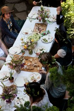 Long table set with lots of flowers and guests with wreaths in their hair. #designsponge and #dssummerparty