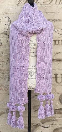 Free Knitting Pattern for Faux Weave Super Scarf - This reversible Purple Super Scarf is made with the Faux Woven Stitch. One size: 10″ (25 cm) wide x 120″ (305 cm) long (including pompom and tassels). Designed by Alexandra Davidoff