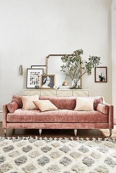 Pink velvet couch, leaning art and vintage mirror, large fluffy rug