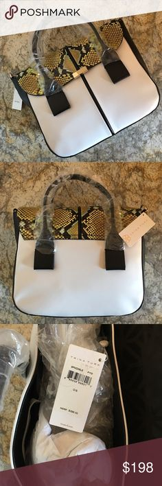 Gorgeous Trina Turk Handbag NWT Beautiful medium sized Trina Turk handbag in white and black leather with yellow/blue snakeskin pattern at the top. This bag has handles, as well as an eye catching leather and chain strap for a shoulder bag look. It's just the perfect length and size. This is brand new, tags still attached and dust bag included. Retails for $398. I'm still debating on keeping this bag for myself, so price is firm. 14x15x5, not including the long shoulder strap. 😉🌸 Trina…
