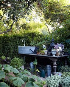 sydney baumgartner created the flower arranging part of her garden in memory of a trip to france, where she toured the garden of nicole de besian, retired fashion stylist at the house of hermes, who spent her retirement years dressing the landscape of her home....crazy about the sink, the zinc finial, the table....