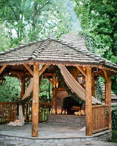 A Tennessee Wedding at the Couple's Log Cabin Home | Martha Stewart Weddings - The travel-loving couple wed in this handmade wooden gazebo that they were inspired to build in their backyard after a trip to Africa. The space was transformed into a rustic altar with the help of heavy linen draping pulled back with lush green garlands and groups of pillar candles at the bottom. The mantel and hearth featured more candles in varying shapes and sizes as fresh logs burned in the fireplace.